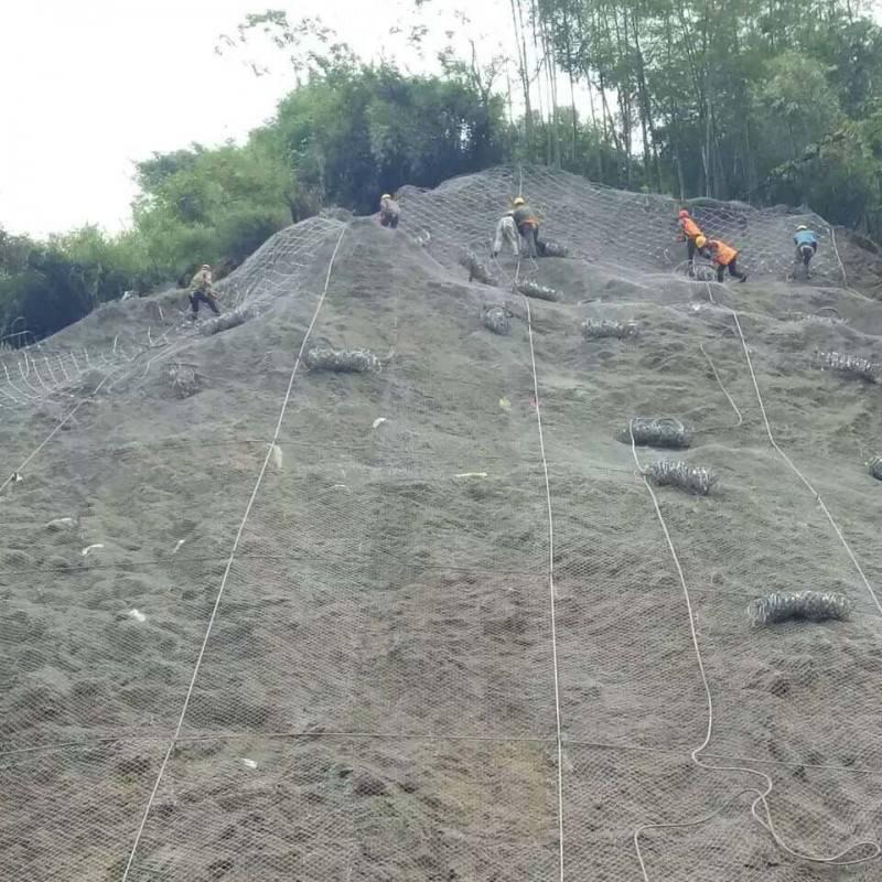 正在山体斜坡上进行四川边坡防护网施工