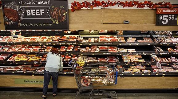 11月26日,美国加州伯班克,一名顾客在沃尔玛超市里挑选牛肉。图片来源:视觉中国