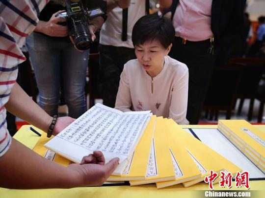 图为甘肃省文物局局长马玉萍参观原版刷印《清敕修大藏经》。 冯志军 摄