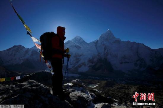资料图:一名登山者站在珠峰前。