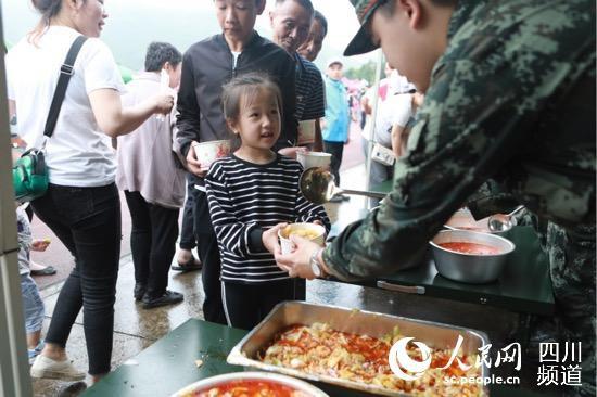 """安置点的孩子领取饭菜后对武警战士说""""谢谢"""""""