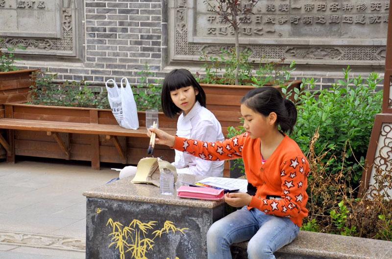 少儿部的学子们正在户外活动中认真作画